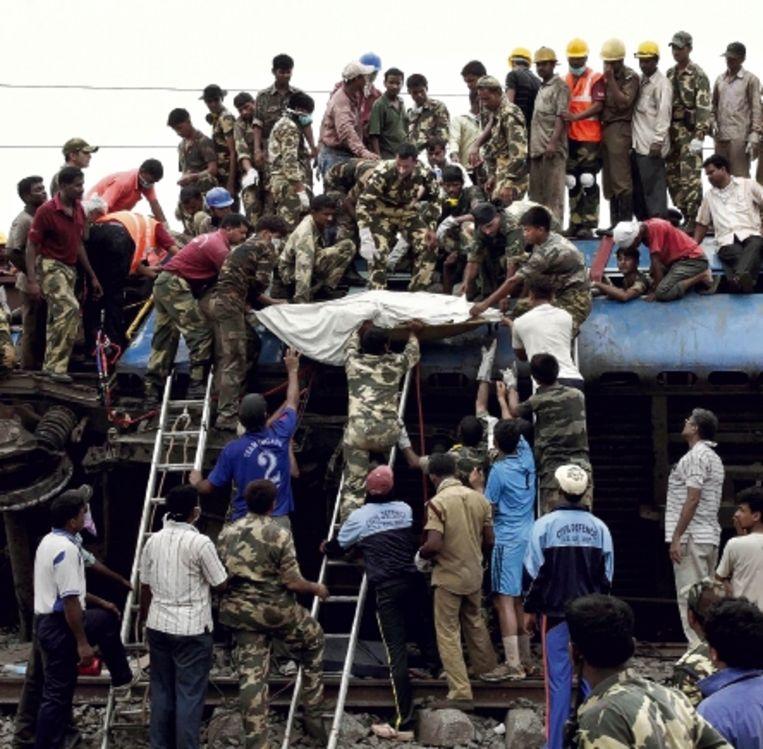 Reddingswerkers halen een lichaam uit de trein die vrijdag door een sabotage-actie ontspoorde. (FOTO AP) Beeld