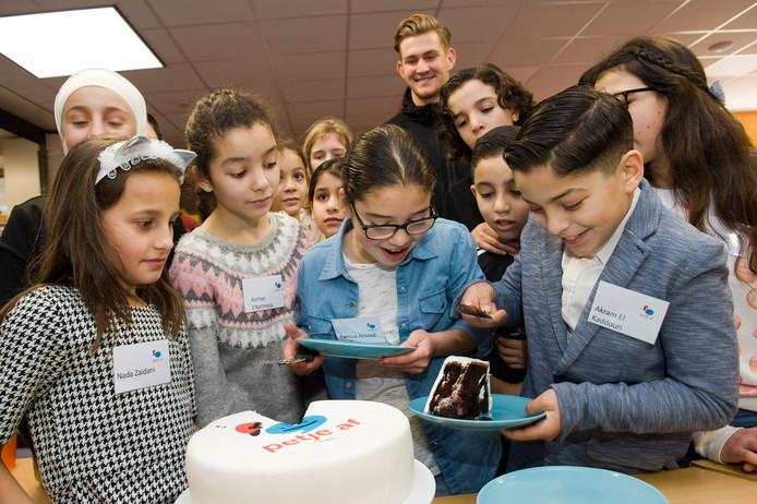 Onder leiding van doelman Mattijs Branderhorst snijden de kinderen van Petje Af een taart aan.