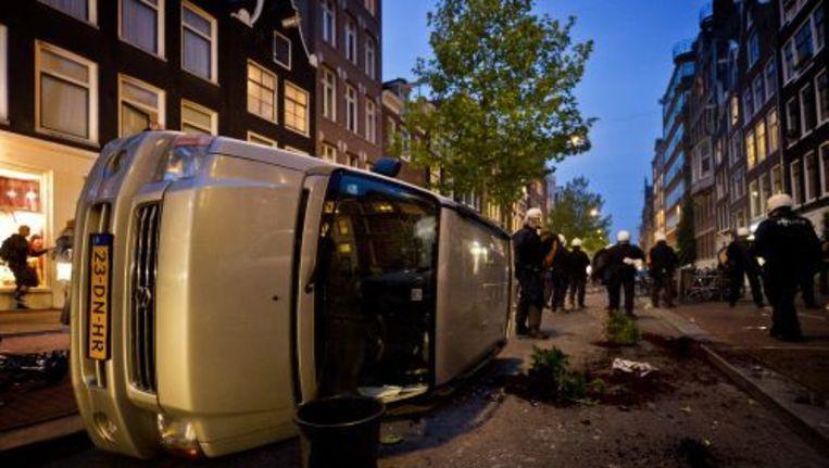 Een auto ligt vrijdagavond in Amsterdam op zijn kant, nadat een demonstratie tegen het kraakverbod uitliep op rellen. ANP Beeld