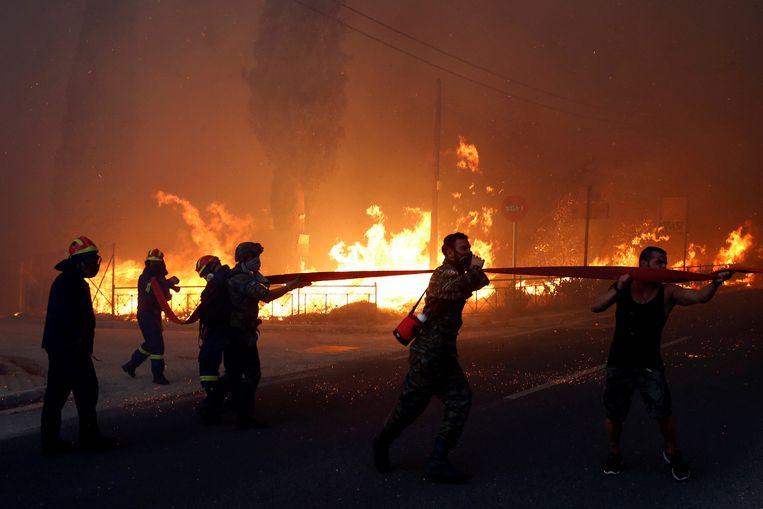 Brandweermannen, soldaten en lokale bewoners proberen met man en mach het vuur te doven. Rafina, Griekenland. Beeld REUTERS