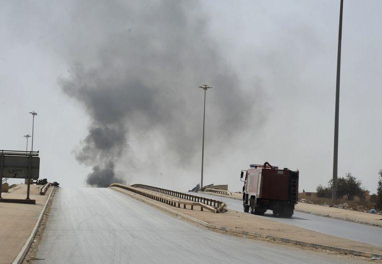 Een brandweerwagen rijdt richting de rook die opstijgt uit Benghazi. Beeld ap