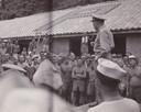 Nederlandse, Britse en Amerikaanse krijgsgevangenen worden bevrijd. Ze luisteren naar een speech van de Amerikaanse commandant.