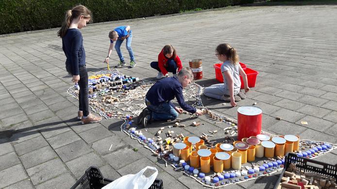 Met houten blokken, wasknijpers, bierdopjes en kurk maken de kinderen een 3D klomp.