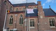 Spandoek aan kerk viseert burgemeester