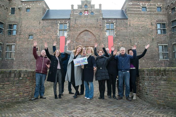 Museumdirectrice Marianne Splint (grijze jas) te midden van haar medewerkers met de cheque die ze kreeg uit handen van zangeres Ilse DeLange, rechts naast haar.