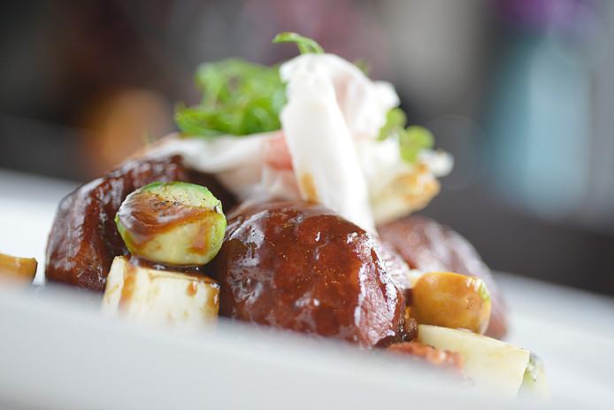 Langzaam gegaarde varkenswang met aardappelmousseline vormt uw hoofdgerecht. Geserveerd met anijspaddenstoelen, Lardo di Collonnata (zacht buikspek),spruiten, gebrande knolselderij, portjus en huisgemaakte dikke frieten.
