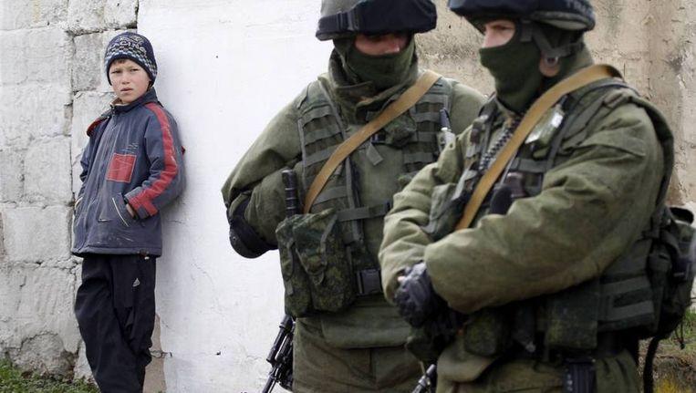 Gewapende mannen staan naast een jongetje bij een militaire basis. Beeld reuters