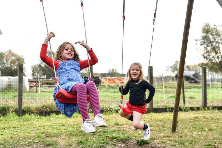 Twee meisjes maken plezier op de schommel in de tuin van de school.