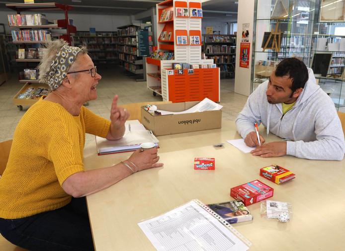Maaike de Lange (links) in gesprek met Karim Olcoidobeid tijdens het Taalcafé in de Hulster bieb.