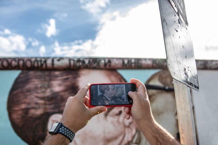 Een toerist neemt een foto van een restant van de Berlijnse Muur aan de East Side Gallery in de Duitse hoofdstad.