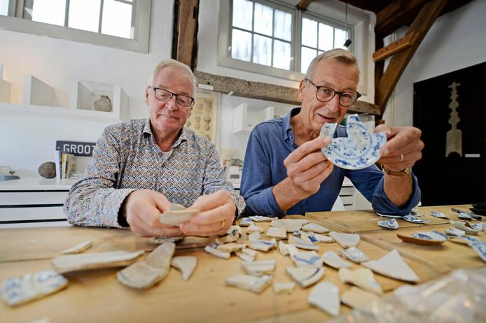 Ben Wubbels (links) en Ruud Olde Dubbelink bestuderen 18de eeuws aardewerk dat gevonden is in de Oldenzaalse bodem.