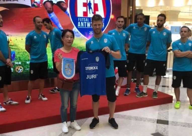 Doelman Xuxa poseert met een local, op de achtergrond kijken zijn ploegmakkers toe.