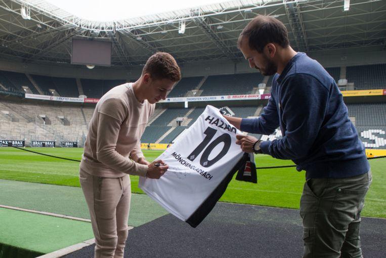 Thorgan Hazard tekent zijn shirt in het gezelschap van onze redacteur Niels Poissonnier.