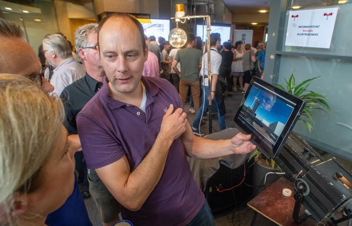 Jeroen Haas, één van de bezorgde omwonenden van Heesch West, toont tijdens de inloopbijeenkomst een visualisatie.