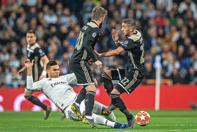 Hakim Ziyech en Lasse Schöne bosten op elkaar als Casemiro een harde tackle op de bal doet. Beeld Guus Dubbelman/ de Volkskrant