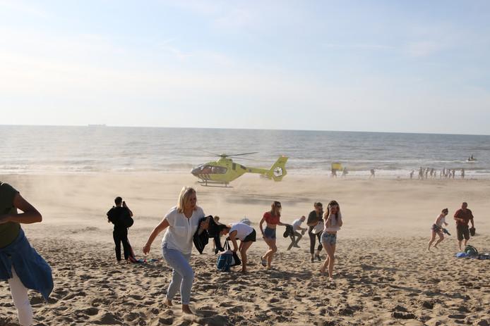 Strandgangers aan  de Wassenaarse Slag ontvluchten de zandstorm die een traumahelikopter veroorzaakt die zwemmers in nood komt helpen.
