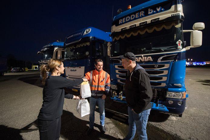 Anieke Vonk (l) van Goudreinet langs de A15 bij Kesteren levert de bestelde maaltijden af aan de chauffeurs.