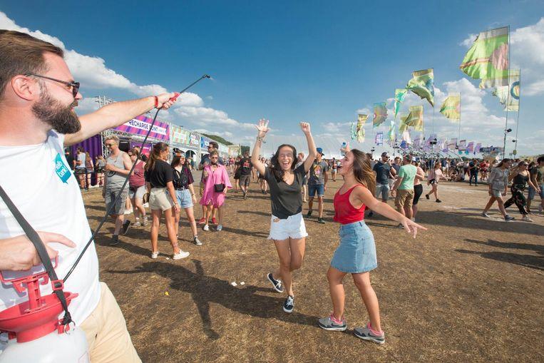 Twee festivalgangers genieten van wat verfrissing op de weide, waar minder volk loopt dan anders.