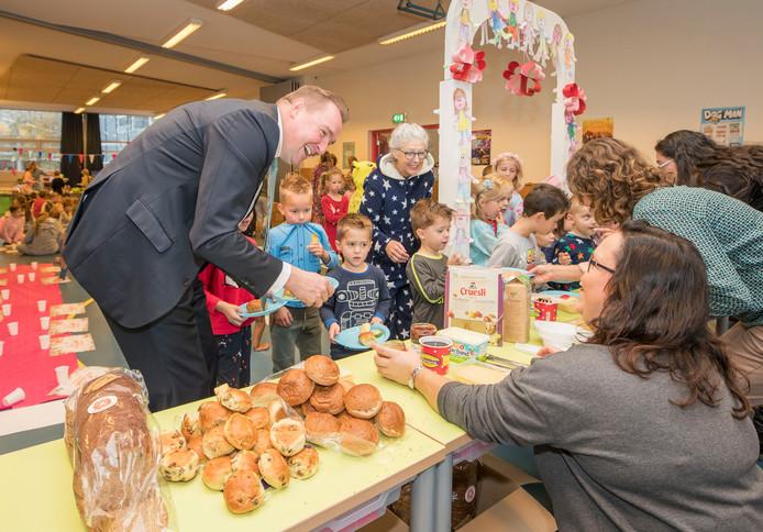 Burgemeester Gerben Dijksterhuis helpt de kinderen bij het ontbijtbuffet van bassisschool De Rank in s'Gravenpolder.