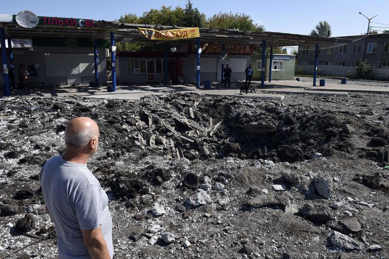 Een man kijkt naar een krater veroorzaakt door een raketinslag bij Makiyivka, ongeveer 15 kilometer van Donetsk. Beeld afp