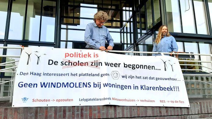 Inwoners van Klarenbeek maken bij de ingang van het stadhuis duidelijk hoe zij denken over de verdeling van zonneparken en windmolens.