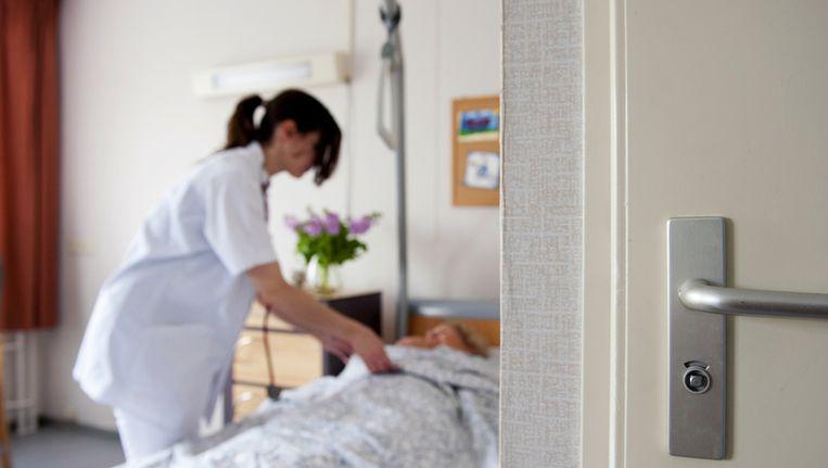 Archieffoto van een verpleegkundige bij een patiënt Beeld anp
