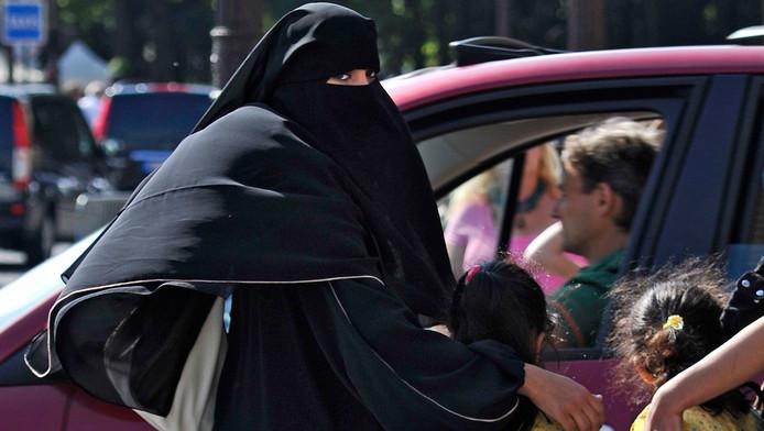 Vrouw gehuld in een niqab haalt in Parijs haar dochtertjes van school. Ook de niqab valt onder het verbod.