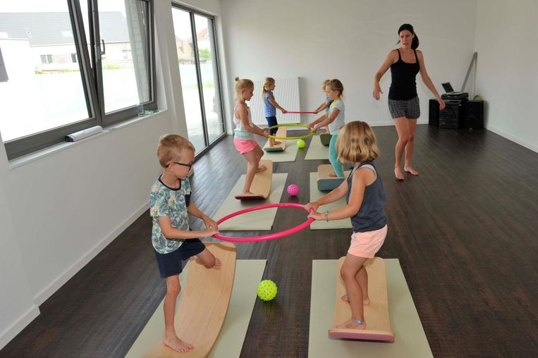 Op een gebogen plank leren de kindjes allerlei bewegingsoefeningen.