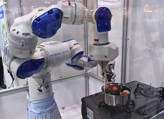 Een robot van een Japans bedrijf geeft een kookdemonstratie op de International Food Machinery and Technology Exhibition in Tokyo