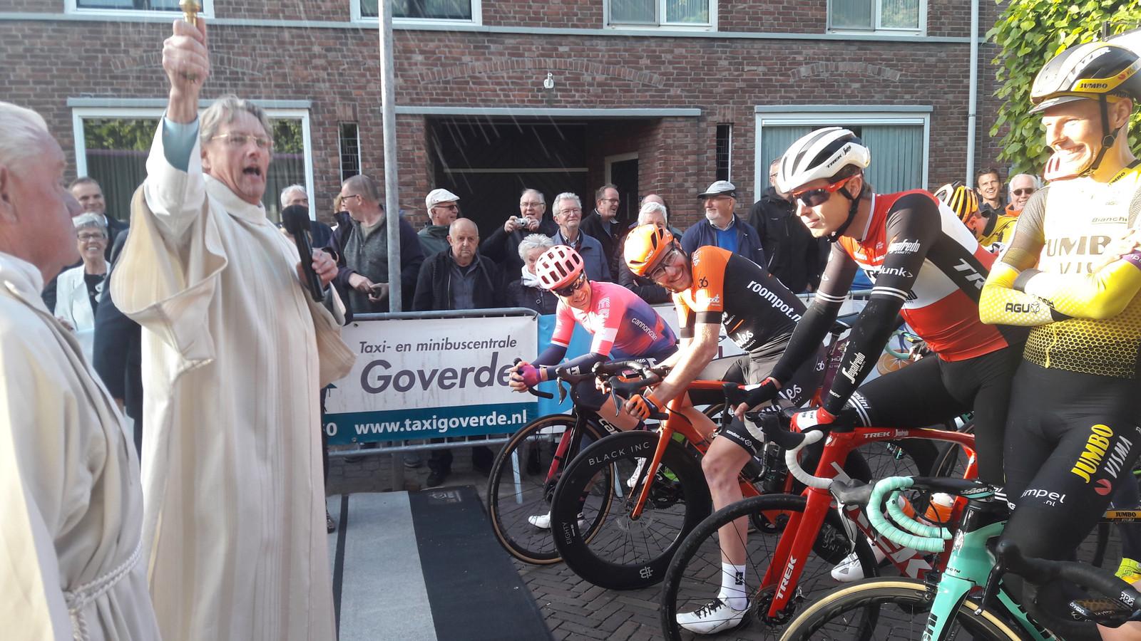 Pastor Ad van Kuyck geeft de profs in Made de zegen mee. Tot  jolijt van de renners.