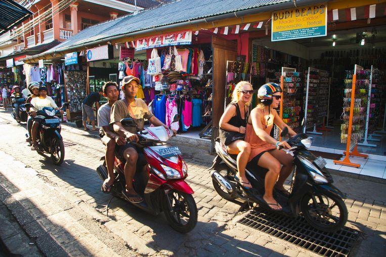 Toeristen op een huurscooter rijden door een straat in Kuta,  Bali, Indonesië. Beeld null