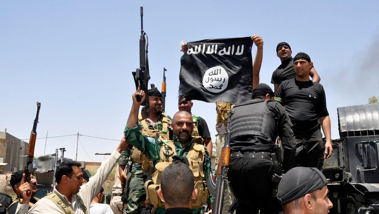 Iraakse soldaten tonen een buitgemaakte IS-vlag. Beeld REUTERS