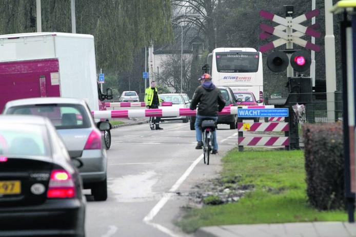 Een fietser wacht voor de spoorbomen bij de overweg in de Rijksweg-Noord in Elst.