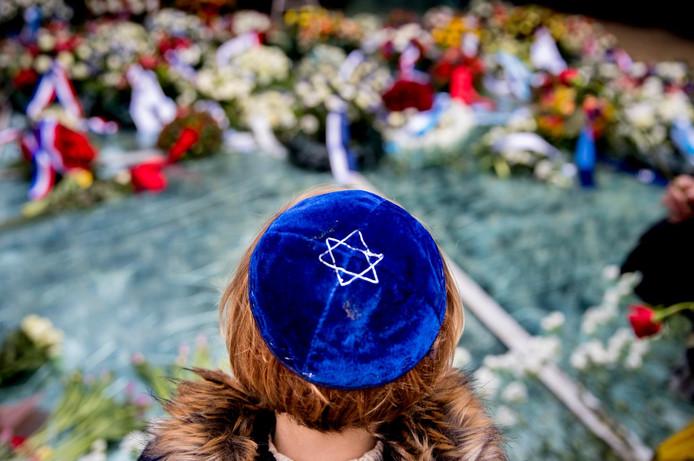 Mensen leggen bloemen bij het Spiegelmonument Nooit meer Auschwitz tijdens de Nationale Holocaust Herdenking.