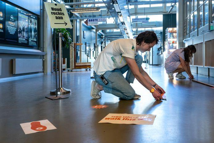 In de Verkadefabriek worden de aanwijzingen voor de looplijnen geplakt. Foto Marc Bolsius