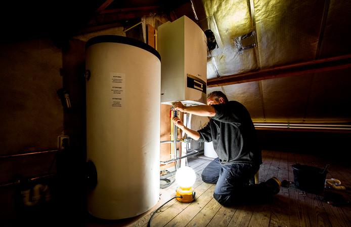 Een erkende installateur is bezig met het installeren van een warmtepomp bij een verwarmingsketel. Ter illustratie.