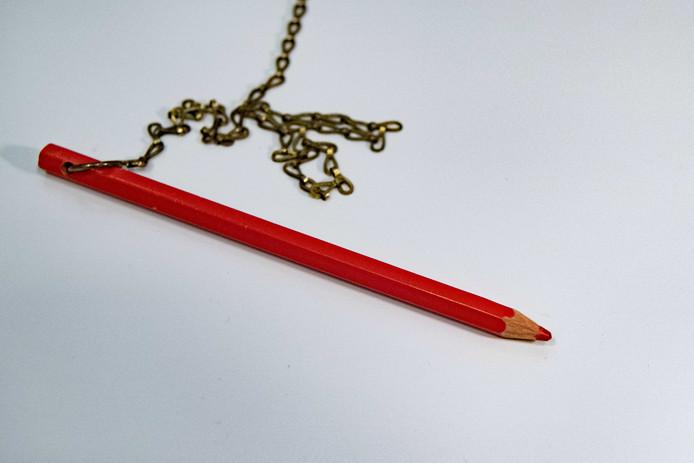 Een rood potlood in een stemhokje bij een stembureau.