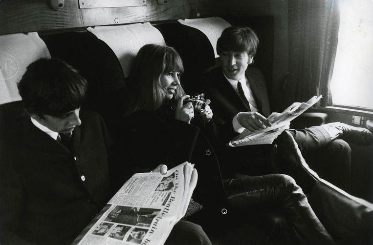 John Lennon and Astrid Kirchherr in de trein tijdens het filmen van A Hard Day's Night. Beeld Max Scheler - K & K/Redferns)