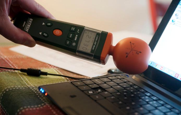 Vader van Floris gebruikt een electromagnetische frequentiemeter om de straling te laten zien in de buurt van een laptop. Foto: Frans Nikkels