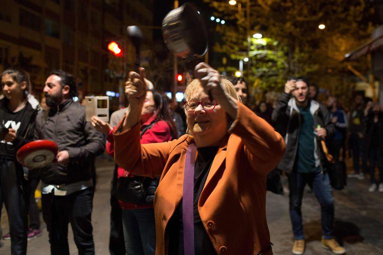 Turken in Istanbul slaan op pannen als protest tegen president Erdogan. De voorlopige referendumuitslag toont een diep verdeeld Turkije. Beeld AFP