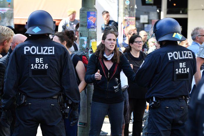 Een demonstrant spreekt politieagenten toe.