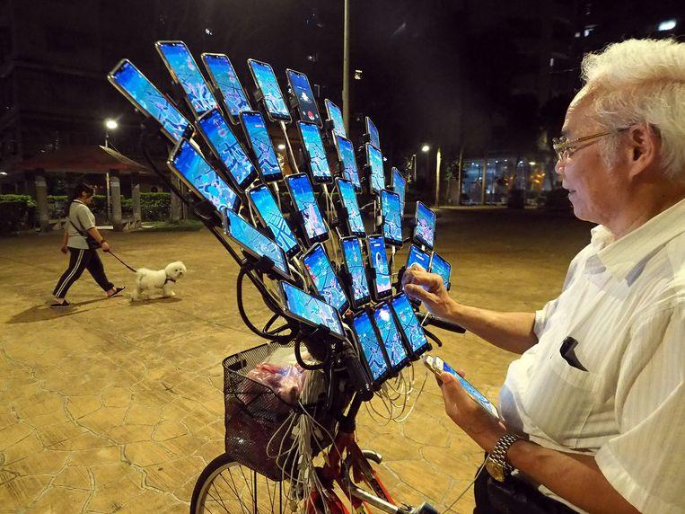 De Taiwanees Chen San-yuan, 70 jaar toen de foto eerder dit jaar werd genomen, is in elk geval verantwoordelijk voor meer dan één download van Pokémon Go: met 29 telefoons op zijn fiets gemonteerd en twee telefoons in de hand vangt hij zo veel mogelijk Pokémon in New Taipei City.   Beeld EPA