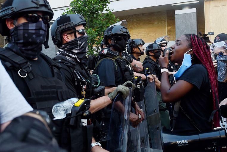 Betogers tegenover de politie nabij het Witte Huis in Washington DC.  Beeld AFP