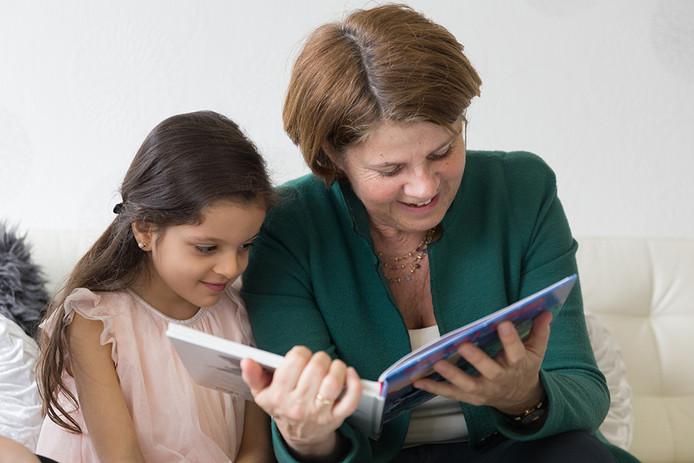 Burgemeester Marja van Bijsterveldt leest voor aan Alaa.