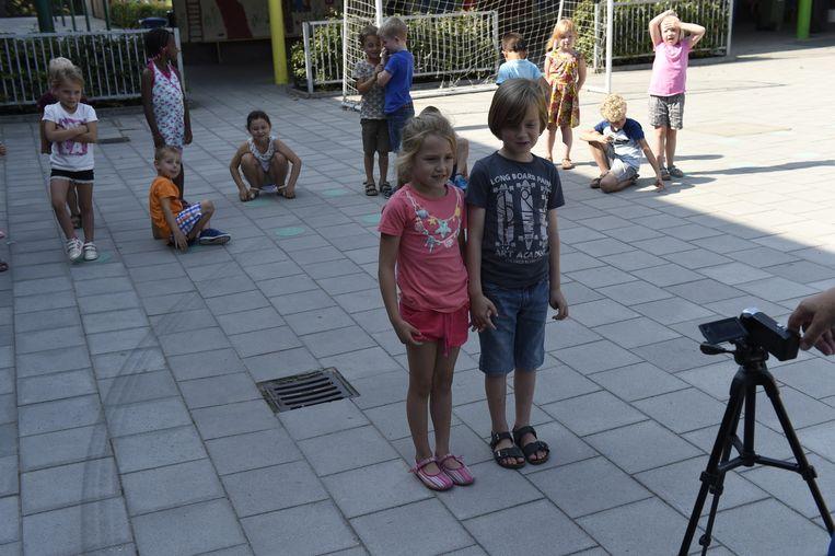 Twee kinderen spraken iets in voor de camera.