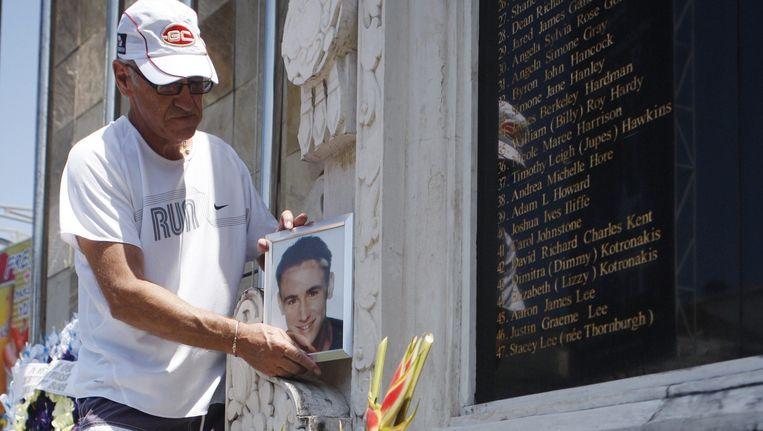 Familielid van een slachtoffer van de bomaanslagen in Bali plaatst een foto bij het herdenkingsmonument in Kuta. Beeld null