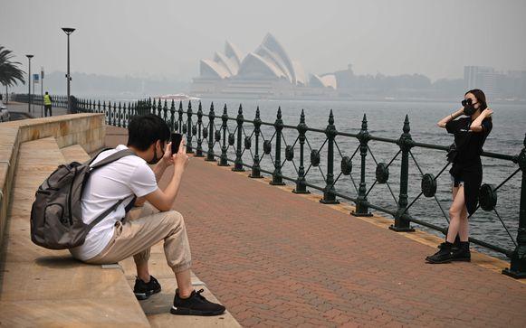 Toeristen maken foto's in Sydney terwijl ze mondmaskers dragen.