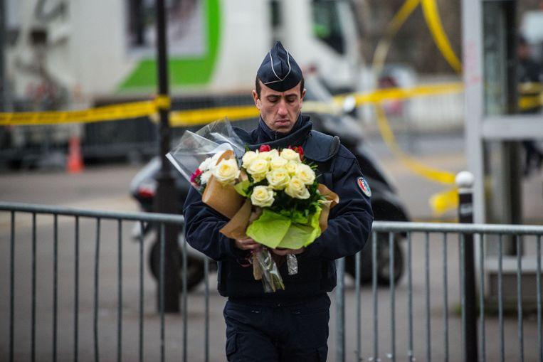 Een politieagent legt bloemen bij de joodse supermarkt in Parijs, waar een gijzeling met dodelijke afloop plaatsvond. Beeld getty