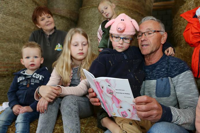 Bert Vreeswijk leest voor aan kinderen tijdens de presentatie van zijn boekje op de kaasboerderij van familie Van Beest in Spijk.