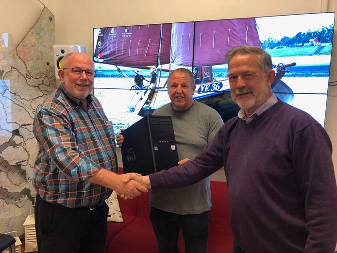 Rinus en Jaap van Stee overhandigen de nieuwe computer aan Leo Pekaar (rechts) van het Oosterscheldemuseum in Yerseke.